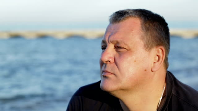 Thoughtful man by the sea Dolly shot of a mature man enjoying seascape with thoughtful look staring stock videos & royalty-free footage