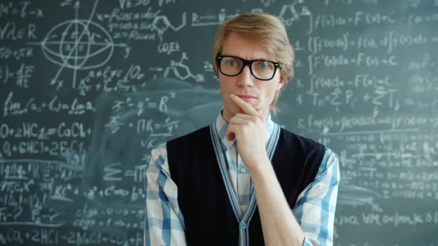 Thoughtful man in glasses raising finger smiling having good idea in classroom Thoughtful man in glasses raising finger smiling having good idea in classroom standing alone with chalkboard in background. People and creativity concept. genius stock videos & royalty-free footage