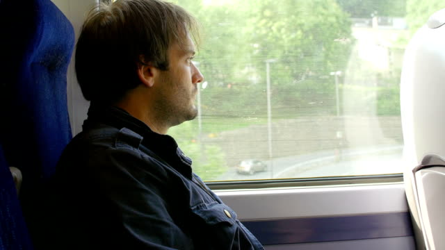 thoughtful man looking outside the window during a train journey video
