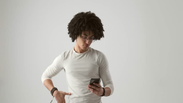 Thoughtful man text messaging on mobile phone Thoughtful man with curly hair text messaging on mobile phone arms akimbo stock videos & royalty-free footage