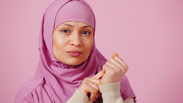 Thoughtful middle aged islamic woman in hijab counting on fingers to five, looking at camera, pink studio background