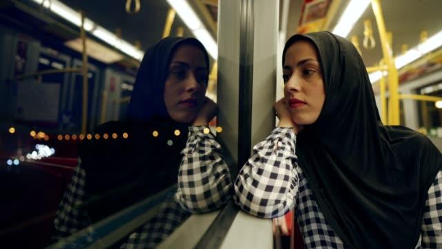Thoughtful Muslim woman in the train