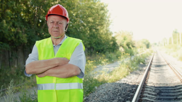 Thoughtful railroader in uniform looking at camera and crossing hands at track video