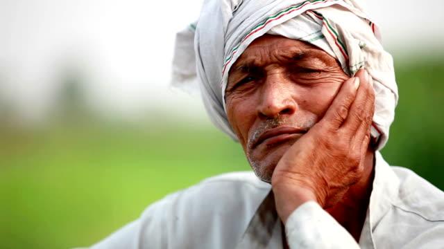 Thoughtful senior farmer close up portrait
