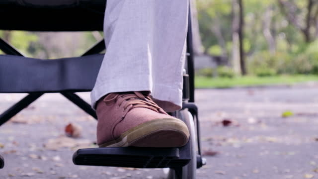 Thoughtful senior man sitting on wheelchair in park. Sad disabled on wheelchair feeling lonely. Retired man alone. video