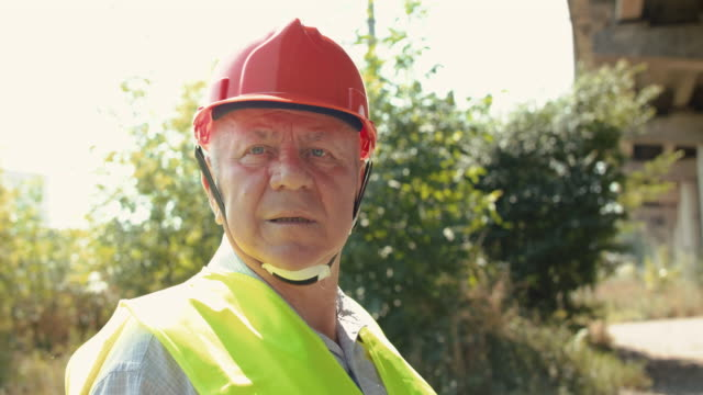 Thoughtful senior railroader in uniform looking around at camera in summer video