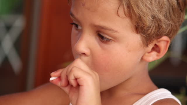 Thoughtful toddler boy with lolipop in mouth