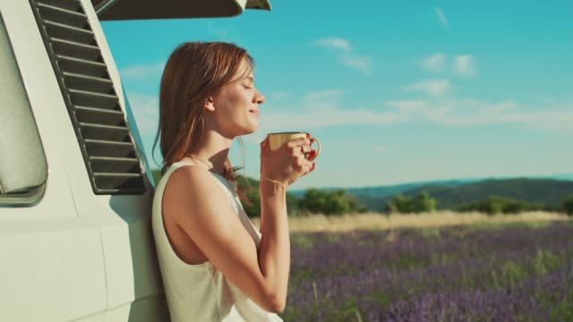 thoughtful woman against van enjoying coffee - campeggio video stock e b–roll