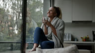 istock Thoughtful woman at home on a cold day drinking tea and looking at the window 1209698786