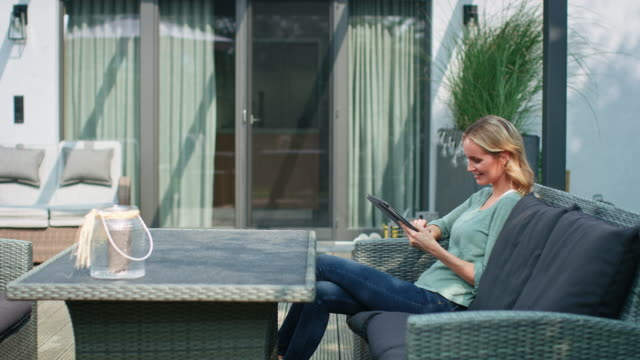 パティオでデジタルタブレットを使用して思慮深い女性 - パティオ点の映像素材/bロール