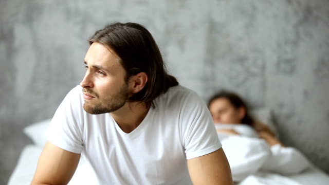 Thoughtful worried man sitting on bed, sleeping woman at background video