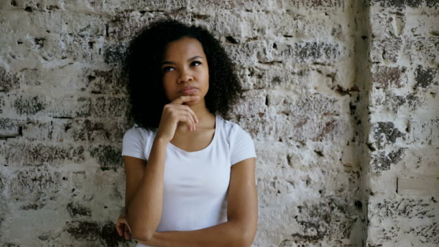 Thoughtful young mixed race girl thinking about solving problem on brick wall background video