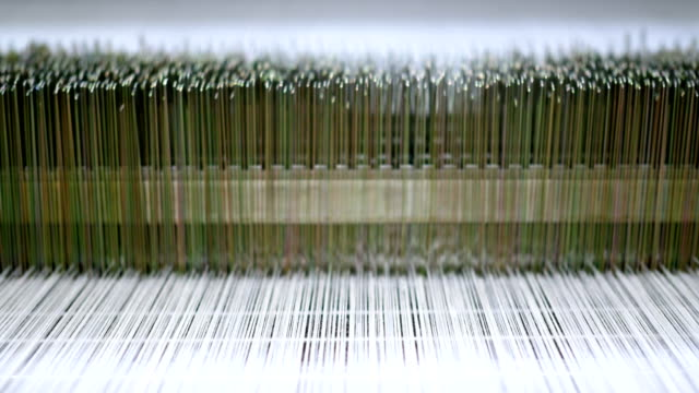 Threads on a loom in  weaving loom machine in textile factory