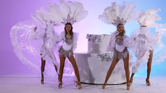 vídeos de stock e filmes b-roll de three adorable women in white snow queen costumes and feather headdresses are dancing near a large cake. dancers posing against a light blue studio background. close up. slow motion - bolo rainha
