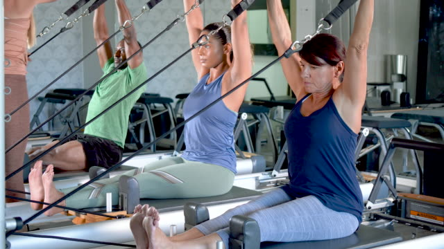 tre adulti nello studio di pilates con istruttore di fitness - braccio umano video stock e b–roll