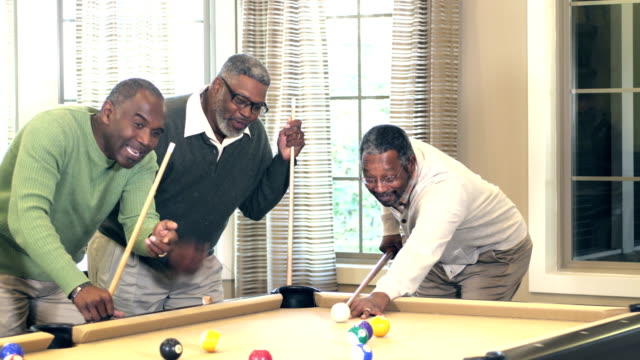 Three African-American men playing billiards