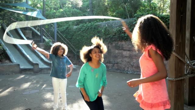 stockvideo's en b-roll-footage met drie afro-amerikaanse zusters springtouw - touw