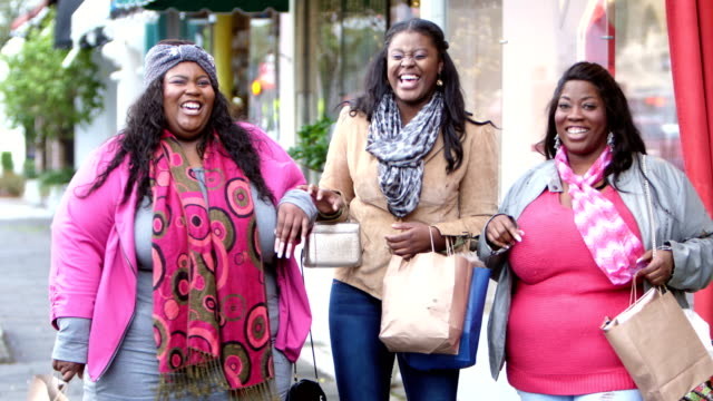 Three African-American women shopping in the city A group of three mid adult African-American women in their 30s shopping in the city, walking on the sidewalk carrying shopping bags, conversing, smiling and laughing. Two of the friends are both large full-figured women. large build stock videos & royalty-free footage