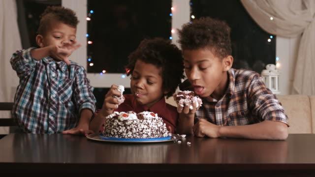 Three afro boys eating cake. video