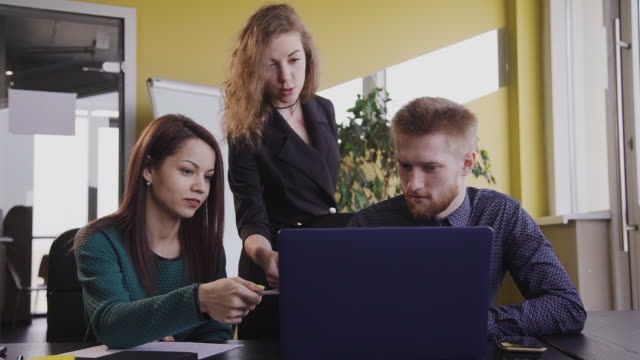 Three american colleagues work and watch on laptop screen at office table