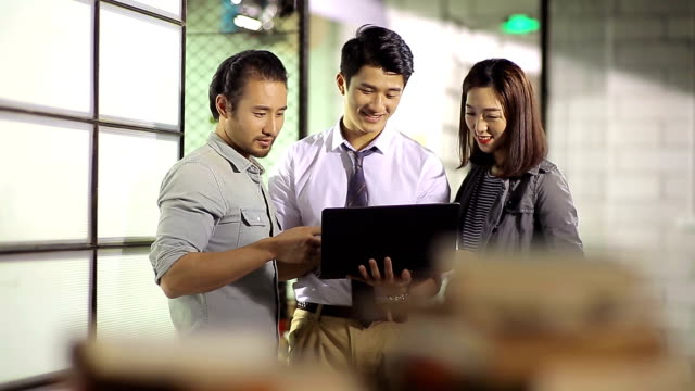 three asian businesspeople discussing business in office - cultura orientale video stock e b–roll