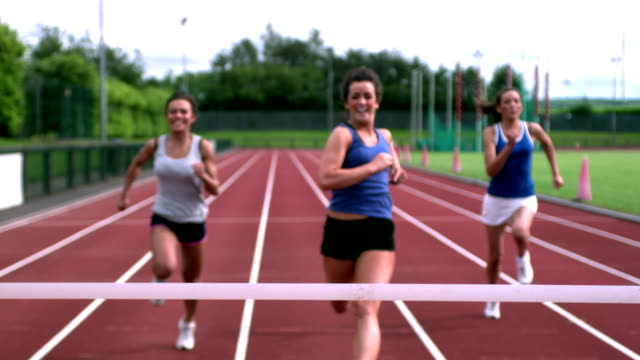 Three athletes running towards the finish line video