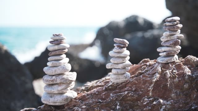 Three balanced pyramids of stones on the beach on the background of sea waves