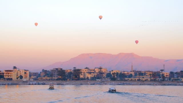 Three balloons flying over the Nile in West Luxor at sunrise, Egypt Luxor, Egypt. Three balloons flying over the Nile in West Luxor at sunrise riverbank stock videos & royalty-free footage