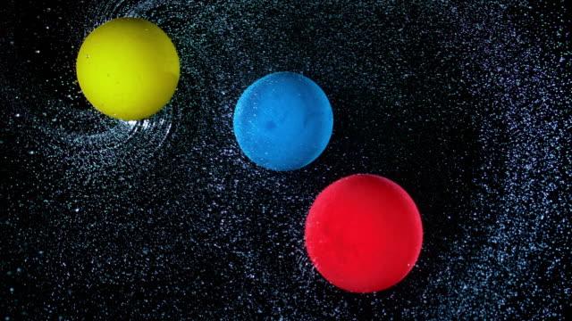 vídeos de stock e filmes b-roll de slo mo ld three balloons rotating across the sky, spraying water and bumping into each other - três objetos