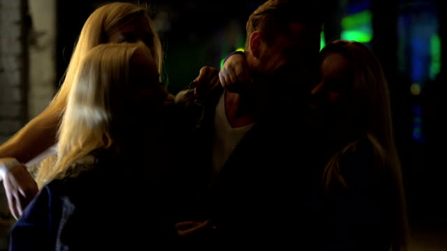Three beautiful blond women flirting with man at night club, relaxation, hook-up video