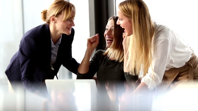 Three beautiful business woman cheering and high-fiving in office meeting video