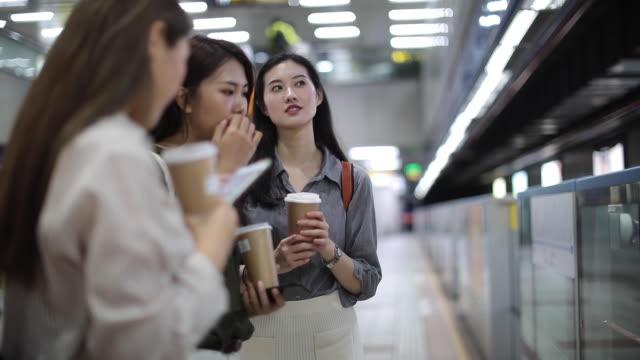 地下鉄の駅に立っている3人の美しい女性の友人 - 乗客点の映像素材/bロール