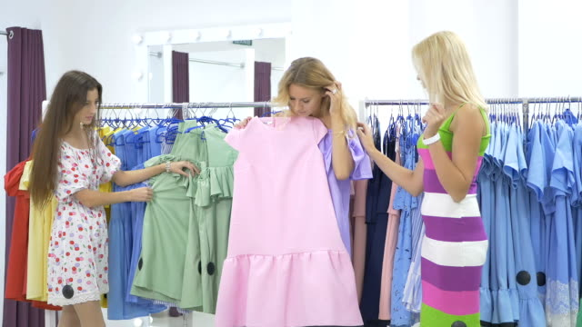 Three beautiful girls fighting over dress in shop video