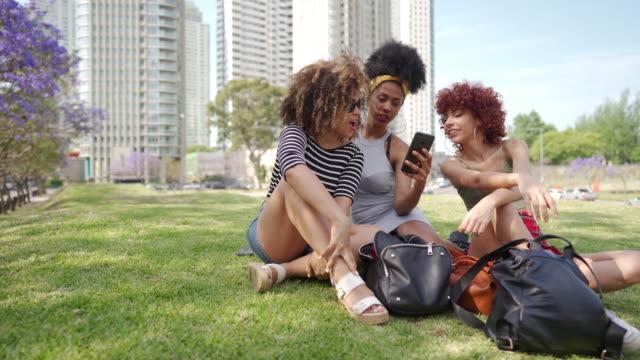 Drei schöne Damen sitzen auf Gras im Park – Video
