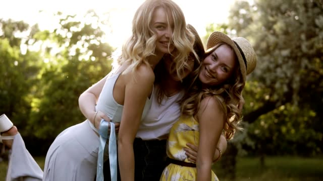 three beautiful women posing for the camera. hugging, smiling. bachelorette concept. girls having fun together in the green park - woman portrait forest video stock e b–roll
