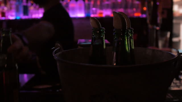 Three beers with limes in a bucket at dark bar video
