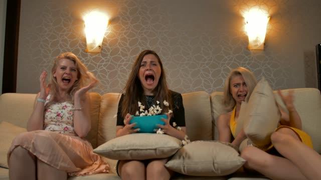 tre bästa vän kvinna på sängen som du tittar på en tv - fruktan bildbanksvideor och videomaterial från bakom kulisserna