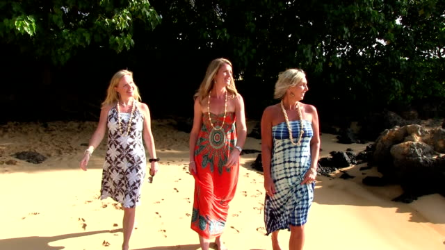 Three blond girls walk on beach in Hawaii slow motion video