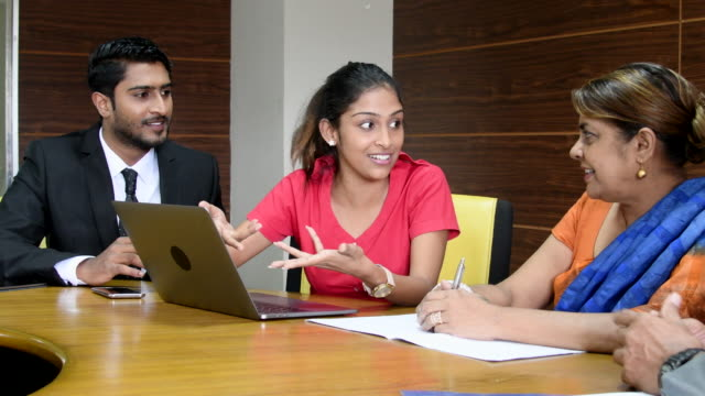 Three business colleagues talking in meeting with laptop Young woman showing mature woman and young male colleague computer screen, she is smiling and pointing as they sit at a table in the meeting room indian culture stock videos & royalty-free footage