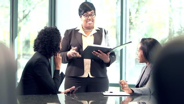 Three business women conversing in board room video