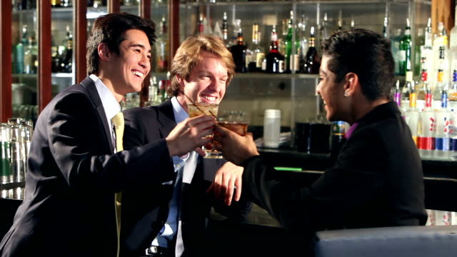 Three businessmen having drinks at bar video