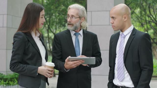 vidéos et rushes de trois hommes d'affaires discuter affaires avec tablette numérique - expliquer