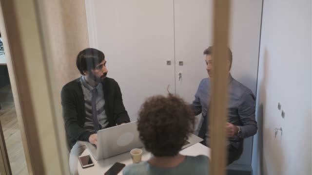 Three businesspeople sitting in a small meeting.