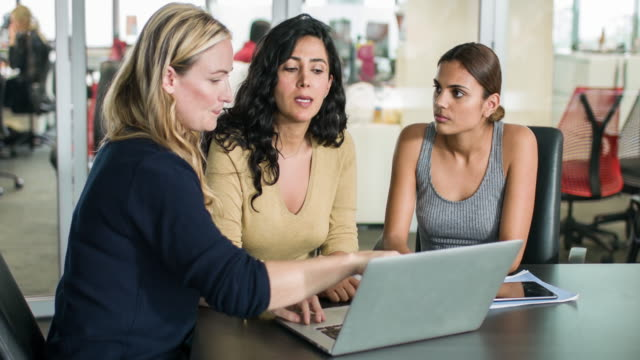 Three businesswomen discussing some work using the laptop video