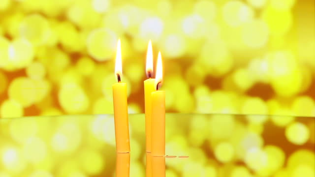 three candles rotating on reflective surface video