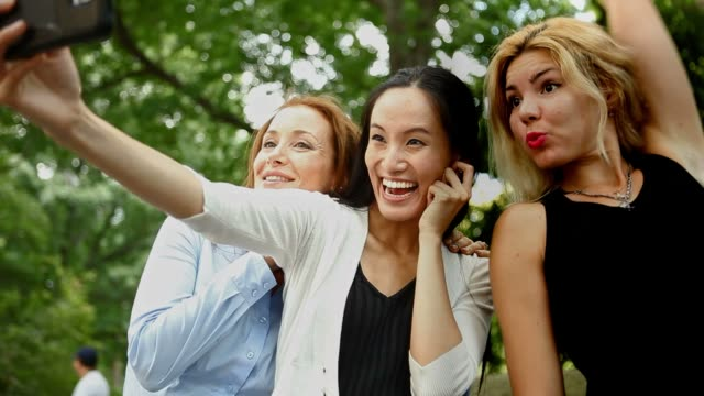 vídeos de stock e filmes b-roll de three cheerful friends taking a selfie outdoors - amizade feminina