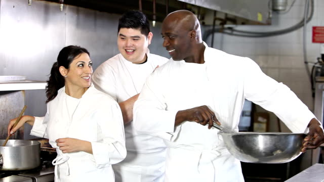 Three chefs cooking and talking in restaurant kitchen video