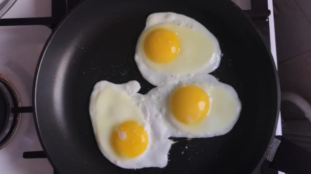 Three chicken eggs being fried on iron skillet. Three organic chicken eggs being fried on iron skillet. View from above. protein stock videos & royalty-free footage