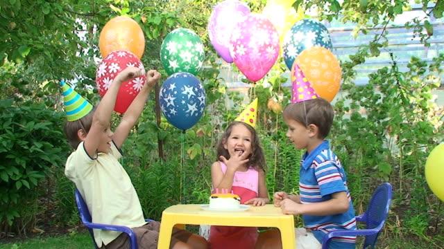 Drei Kinder auf einer Geburtstagsfeier im Garten – Video