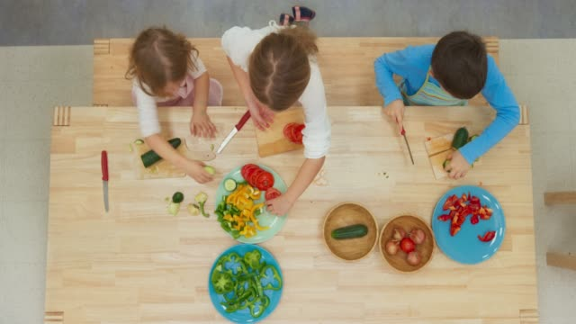 LD Three children cutting vegetables at the table